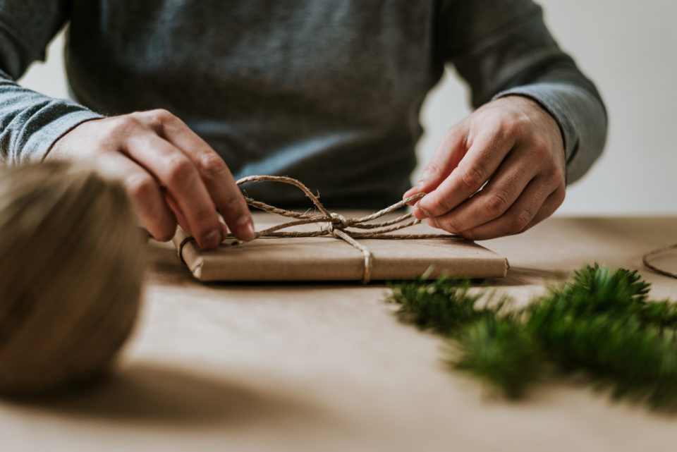 Close-up of male hands wrapping present with eco-friendly materials.