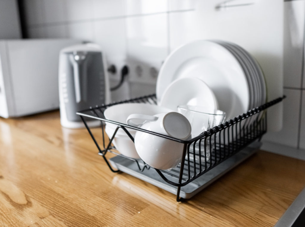 Dish rack with dishes inside, on kitchen counter