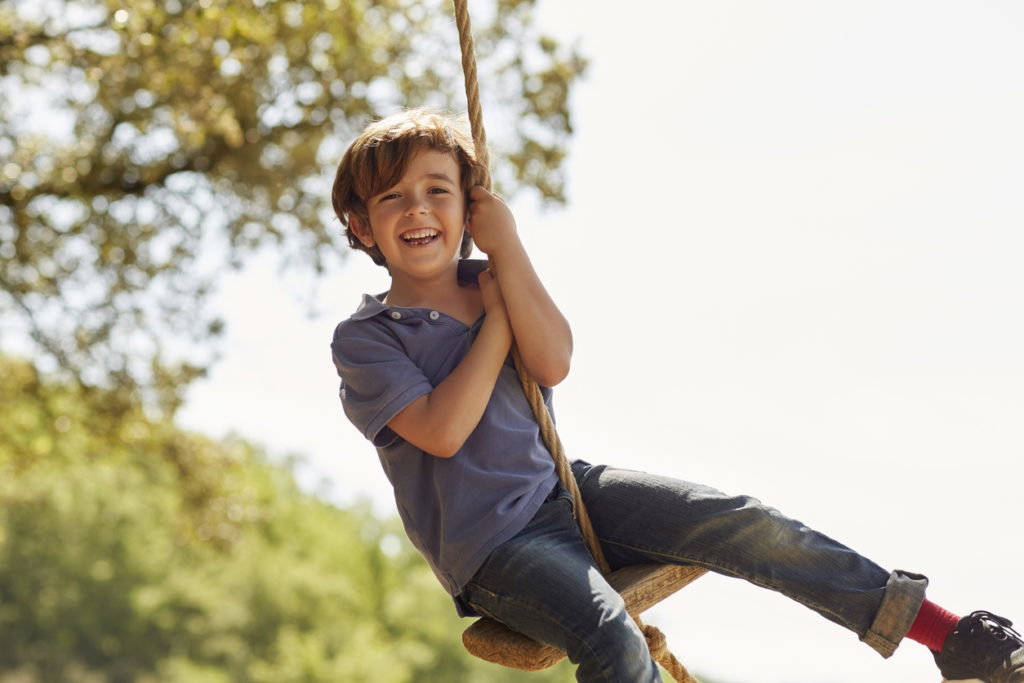 Portrait of cheerful boy playing on swing.