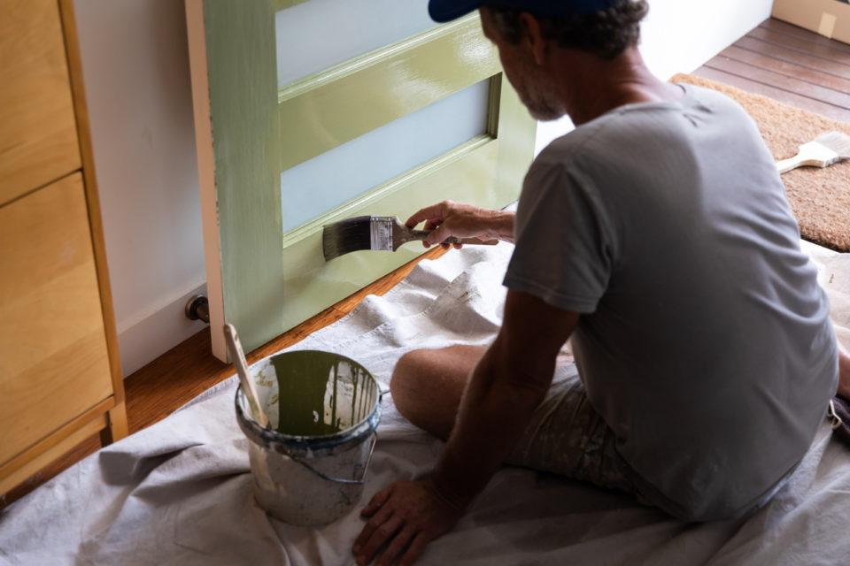 Man painting front door olive green