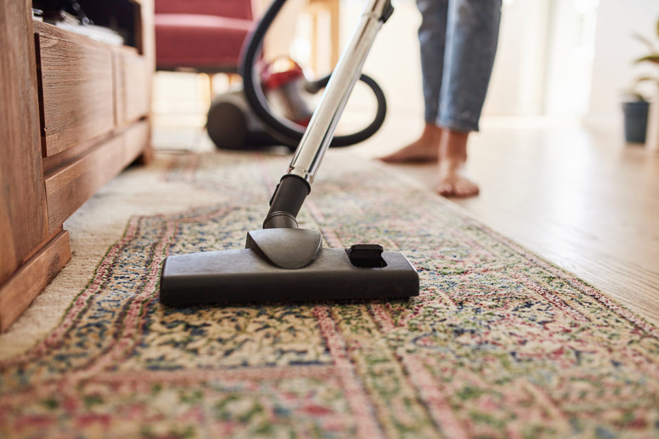 Shot of a young woman vacuuming the living room at home