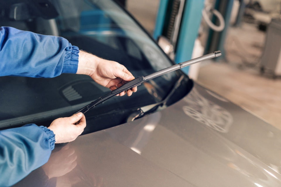 Technician changing windshield wipers on a car