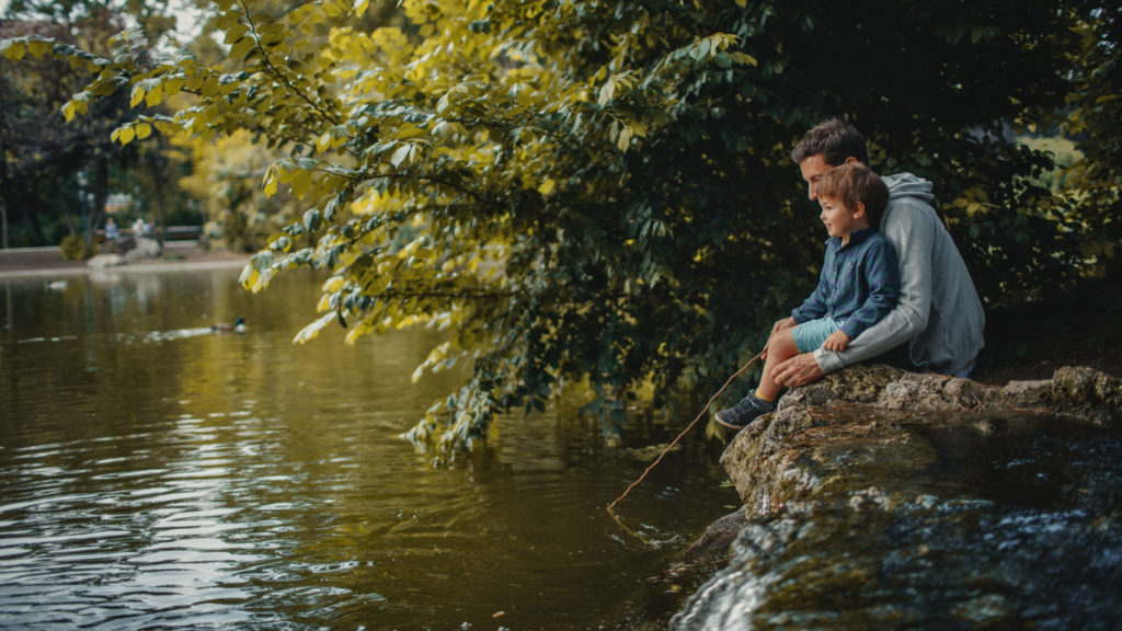 Little smiling boy is learning how to catch a fish in a park pond