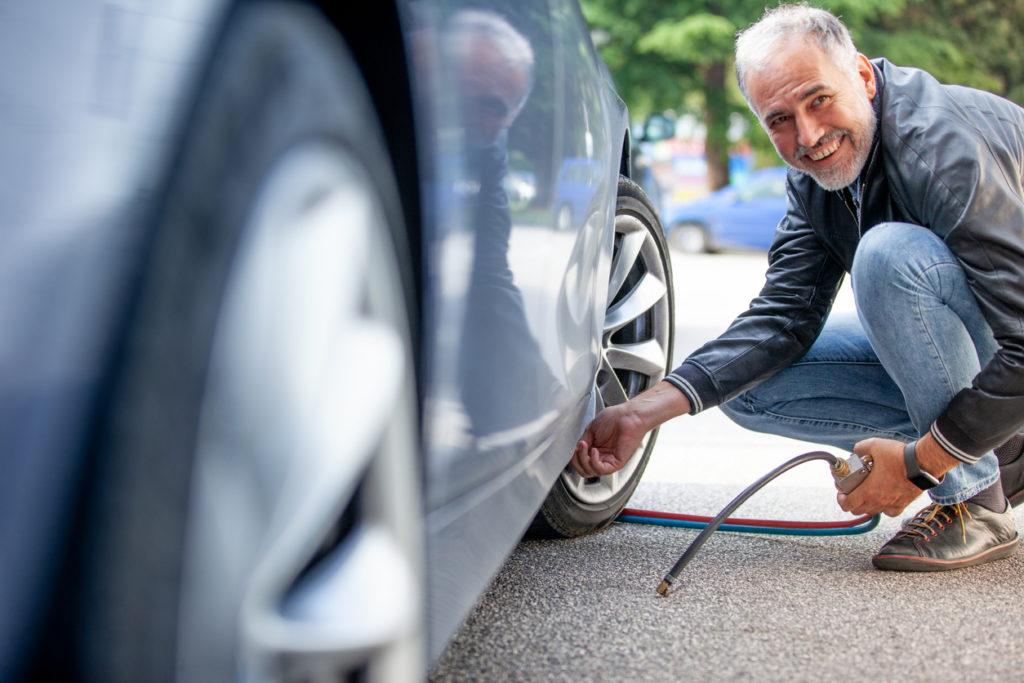 Smiling Mature Man Inflating Car Tires Outdoors